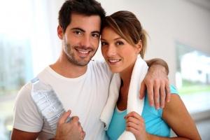 Homem e mulher na academia. Ele segura uma garrafa de água e ela tem uma toalha enrolada no pescoço.